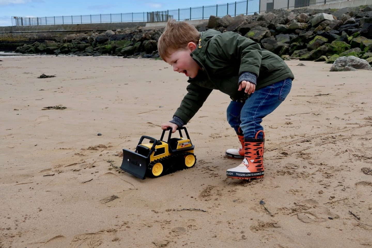 A young child pushing a large bulldozer toy on the beacj