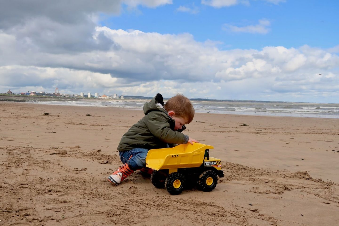 A child with a yellow Tonka truck on the beach