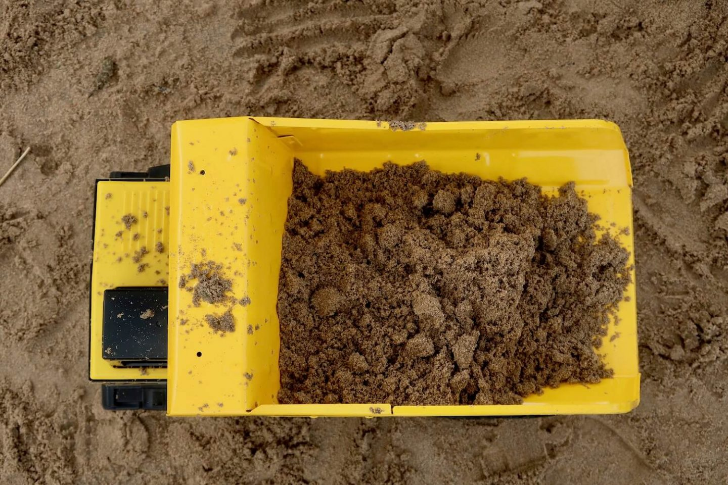 A top down view of a large Tonka Dump Truck filled with sand on the beach.