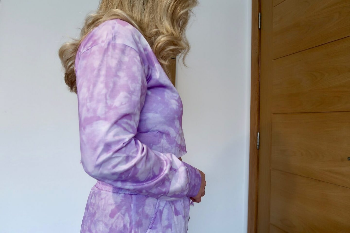 A side view of the torso of a woman wearing a purple and white tie dyed loungewear set