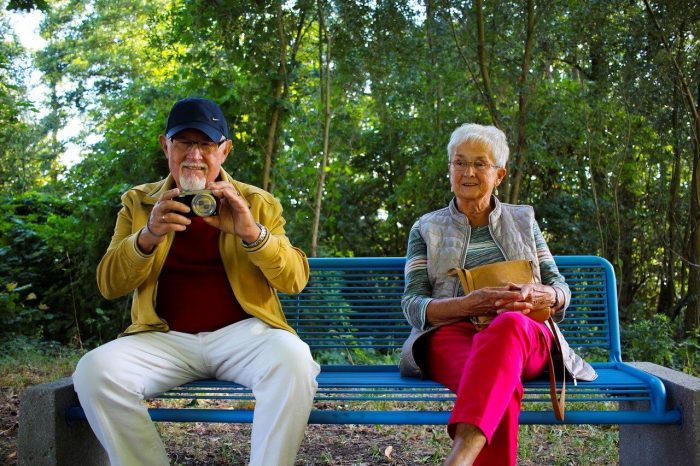 An older man and woman sit on a blue bench in a wooded park. The man has a camera up and the woman i sholding a bag.